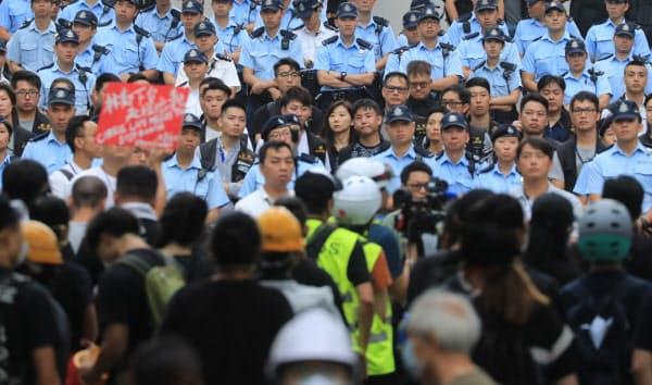 立法会前で警察(奥)とにらみ合うデモ隊(17日午前、香港)=三村幸作撮影