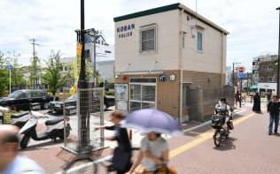 警察官が刺され拳銃が奪われた千里山交番の前を通る人たち(17日、大阪府吹田市)