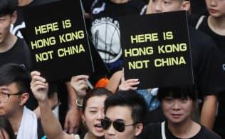 「ここは香港だ。中国ではない」と書かれたプラカードを掲げ、デモ行進する人たち(16日、香港)=三村幸作撮影