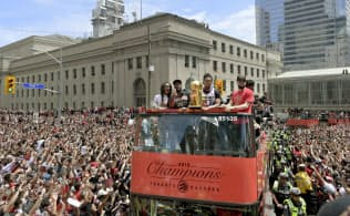 NBA決勝を制し、優勝パレードで沿道のファンに祝福されるラプターズの選手ら(17日、トロント)=USA TODAY