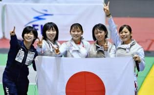 女子フルーレ団体で優勝し、日の丸を手に笑顔で写真に納まる(左から)宮脇、上野、東、辻、菊池(18日、千葉ポートアリーナ)=共同