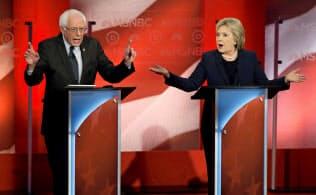 2016年の民主党大統領候補討論会で論戦を繰り広げるサンダース氏(左)とクリントン氏=ロイター