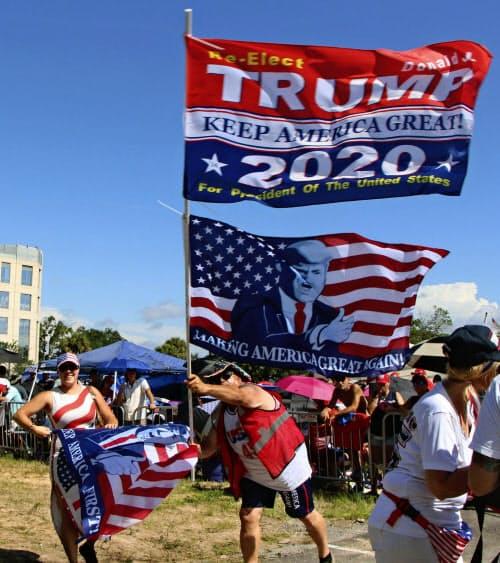 18日、米フロリダ州オーランドの集会会場近くで、トランプ大統領の再選を訴える旗を振る支持者(共同)
