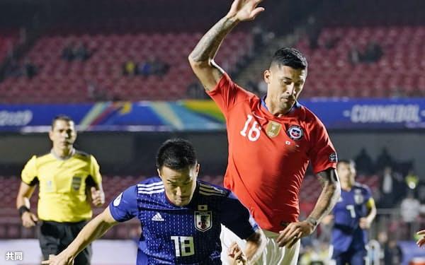 南米選手権の日本―チリ戦の後半、競り合う岡崎(手前)=共同
