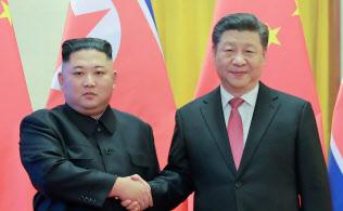 1月の北京での首脳会談で握手を交わす中国の習近平国家主席(右)と北朝鮮の金正恩委員長=ロイター