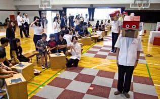 村田製作所の体験型教室。ロボット役の社員が児童の指示通りに動く(京都府長岡京市)