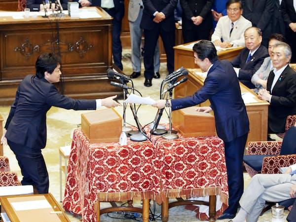 国民民主党の玉木代表(左)から渡された金融審議会の報告書を返す安倍首相(19日、国会内)