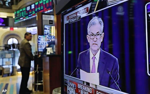 パウエルFRB議長の会見を映すニューヨーク証券取引所のモニター(19日)=AP