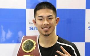 4階級制覇を果たした試合から一夜明け、笑顔でポーズをとる井岡一翔(20日、東京都内)=共同