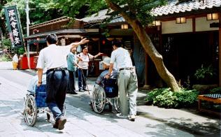 ボランティアらと外出先のそば屋に入るデイサービス利用者(東京・調布市の深大寺で)