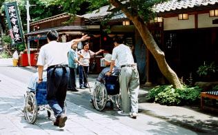 ボランティアらと外出先のそば屋に入るデイサービス利用者(東京?調布市の深大寺で)