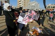 トランプ米大統領、イスラエルのネタニヤフ首相の写真を燃やして抗議するパレスチナの人々(18日、ガザ)=ロイター