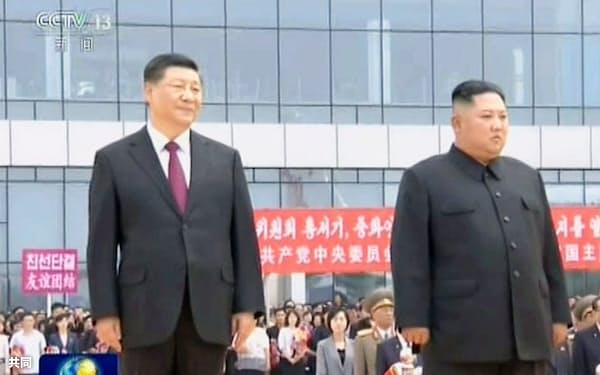 中国中央テレビが20日放映した、北朝鮮の金正恩朝鮮労働党委員長(右)と歓迎式典に臨む中国の習近平国家主席(共同)