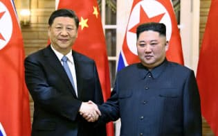 平壌で握手する中国の習近平国家主席(左)と北朝鮮の金正恩朝鮮労働党委員長(20日)=新華社・共同