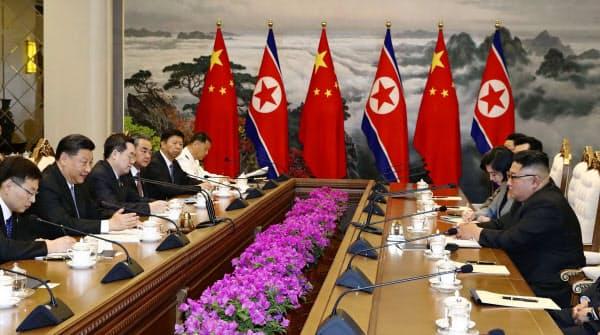 会談する中国の習近平国家主席(左手前から2人目)と北朝鮮の金正恩朝鮮労働党委員長(右端)=20日、新華社・共同