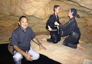 沖縄県読谷村のユンタンザミュージアムの自然壕「チビチリガマ」を再現したジオラマと村教委文化振興課の上地克哉課長(14日)=共同