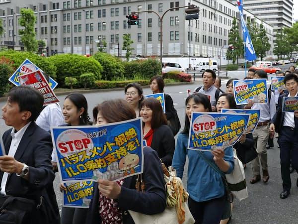 ハラスメント根絶に向け、ILO条約案の支持を訴える人たち(5月、東京・霞が関)=共同