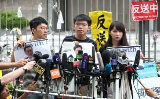林鄭月娥行政長官の記者会見を受け、報道陣を前に抗議する黄之鋒氏(ジョシュア・ウォン)(中)ら(18日、香港)=樋口慧撮影