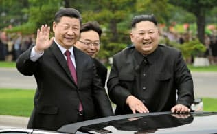 オープンカーから沿道の市民に手を振る習近平国家主席と金正恩委員長(右)(20日、平壌)=朝鮮中央通信・共同