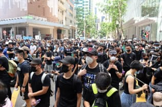 21日、香港警察本部の前で抗議する若者ら