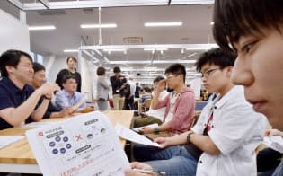 企業の担当者(左側)から課題について説明をうける学生(大阪市北区)