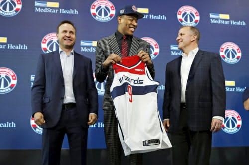 NBAのドラフト会議でウィザーズから日本人初となる1巡目指名を受け、記者会見でユニホームを手に笑顔の八村塁=中央(21日、ワシントン)=AP