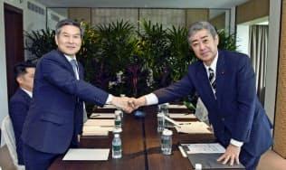 非公式会談で握手する岩屋防衛相(右)と韓国の鄭景斗国防相(6月1日、シンガポール)=韓国国防省提供・共同