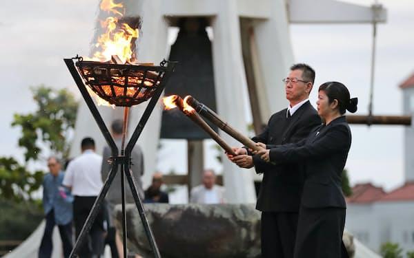 沖縄全戦没者追悼式の前夜祭で「鎮魂の火」をともす遺族代表(22日、沖縄県糸満市の平和祈念公園)