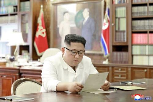 トランプ米大統領から送られた親書を読む金正恩委員長=朝鮮中央通信・ロイター