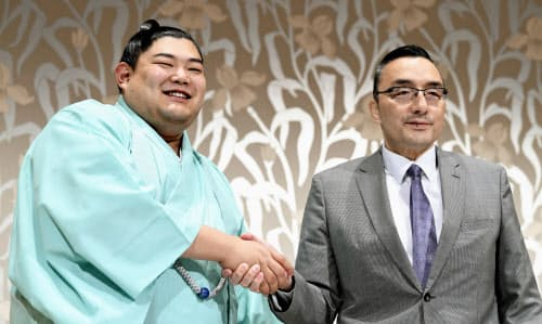 大相撲名古屋場所の番付が発表され、記者会見で錣山親方(右)と握手する新小結の阿炎(24日、名古屋市)=共同