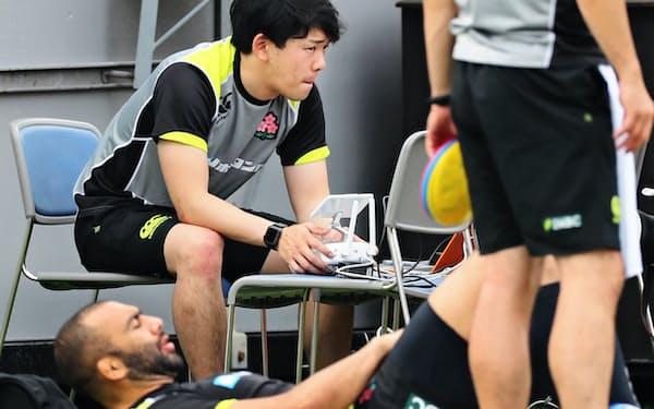 浜野さん(奥)はデータ面からラグビー日本代表を支える=宮崎市