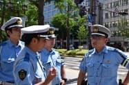 交通規制を実施する交差点で、打ち合わせをする石川県警と大阪府警の警察官(24日、大阪市中央区)