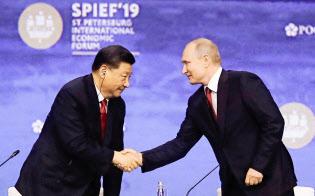 6月7日、サンクトペテルブルク国際経済フォーラムで握手する習近平・国家主席(左)とプーチン大統領=AP