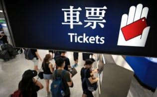 個人情報の追跡を防ぐため、デモ参加後の電車切符を現金で買う人たち(16日、香港)=三村幸作撮影