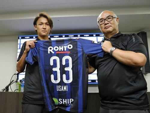 G大阪に復帰し、記者会見でユニホームを手にする宇佐美。右は山内隆司社長(25日、大阪府吹田市)=共同