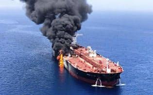 13日、ホルムズ海峡付近で攻撃を受けて火災を起こし、オマーン湾で煙を上げるタンカー=AP