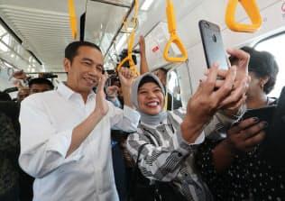 大量高速輸送システム(MRT)を視察し、乗客と写真を撮るインドネシアのジョコ大統領(左)(25日、ジャカルタ)=石井理恵撮影