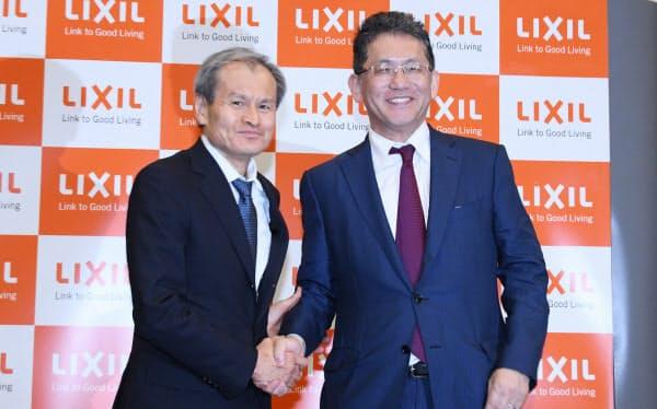 記者会見で握手するLIXILグループの瀬戸欣哉CEO(右)と松崎正年取締役会議長(25日、東京都中央区)