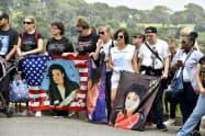 マイケル・ジャクソンさんの墓地前で似顔絵を掲げるファンら(25日、米カリフォルニア州グレンデール)=共同