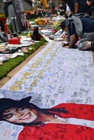マイケル・ジャクソンさんを追悼し、横断幕にメッセージを書き込む男性(25日、米カリフォルニア州グレンデール)=共同