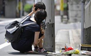 女児が虐待を受け、亡くなった自宅アパートに花を手向けにきた親子(2018年6月、東京都目黒区)=共同