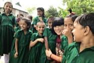 バングラデシュのナマプティア村で建設した小学校の子どもたちに囲まれ、ほほえむ美砂子さん(右から3人目、2018年8月)=共同