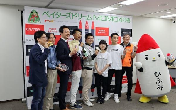 モモ4号機の打ち上げを発表したインターステラテクノロジズの稲川貴大社長(左から5人目)ら(26日、東京・品川)