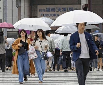 福岡・天神の繁華街で傘を差して歩く人たち(26日午後)=共同
