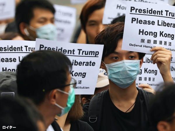デモ参加者は「トランプ大統領、香港を解放してください」と書かれたプラカードを掲げた(26日、香港)=ロイター