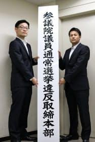 看板を設置する捜査員(27日午前、東京都千代田区)