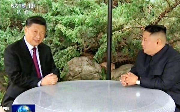 中国中央テレビが放映した、平壌で会談する中国の習近平国家主席(左)と北朝鮮の金正恩委員長=共同