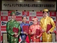 記者会見するクックビズの藪ノ賢次社長(右)とベトナム提携先の関係者(27日、東京・千代田)