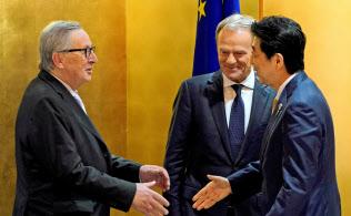 安倍首相と握手するユンケル欧州委員長(左)。隣はトゥスクEU大統領(27日、大阪市)=ロイター