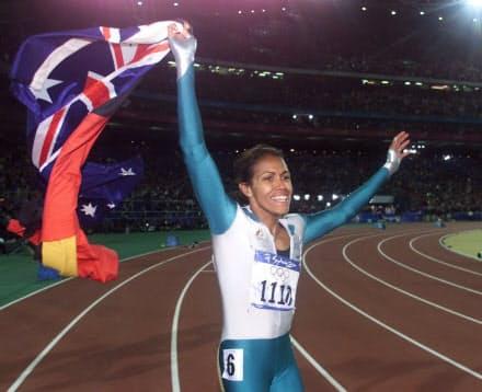 シドニー五輪の女子400メートルで優勝し、オーストラリアとアボリジニの旗を手に、観客の声援にこたえるフリーマン=ロイター